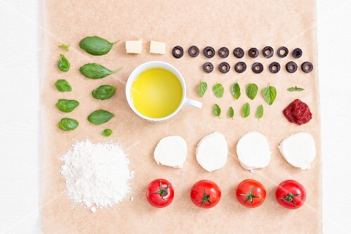 Rows of various pizza ingredients on a piece of baking paper