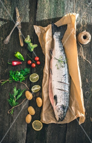 Fresh salmon on a piece of paper next to ingredients (seen above)