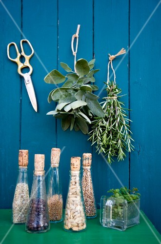 Glass bottles of seeds against a wooden wall hung with bunches of herbs