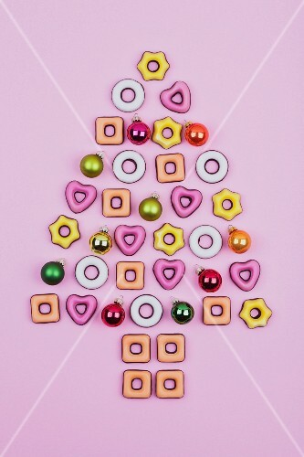 Christmas cookies and baubles on a pink surface in the shape of a Christmas tree
