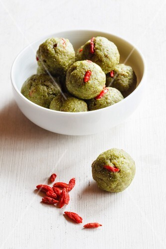 A bowl of matcha energy bites made with coconut, dates and almonds