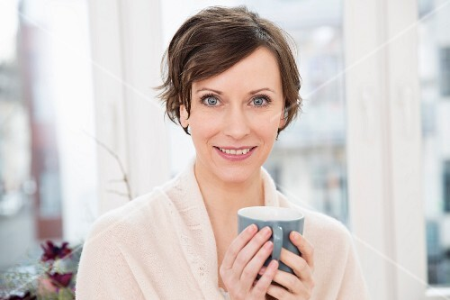 A smiling woman holding a cup of coffee