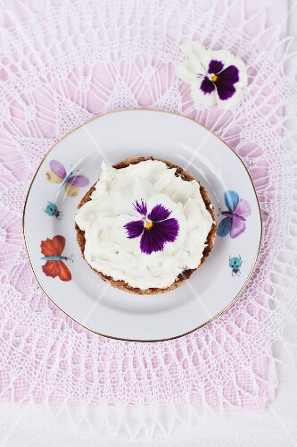 A slice of bread topped with cream cheese and edible pansies