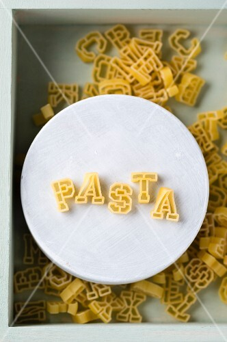 The word 'Pasta' spelt with alphabet pasta on a plate (seen from above)