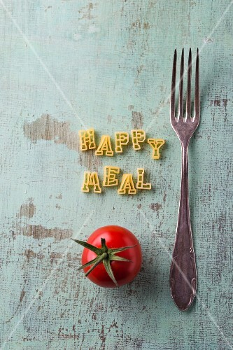 The words Happy Meal spelt with alphabet pasta next to a fork and a tomato