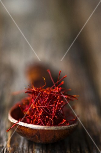 Saffron threads on a wooden spoon (close-up)
