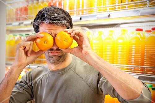 A man standing in front of a chiller cabinet with rows of juice bottles in a supermarket holding two oranges in front of his eyes