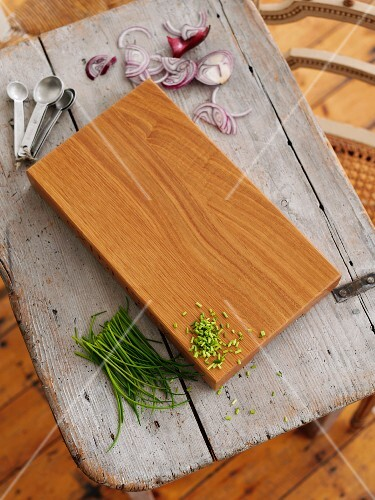 A wooden board with chives, red onions and measuring spoons