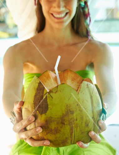 A young woman wearing a beach dress holding a fresh coconut