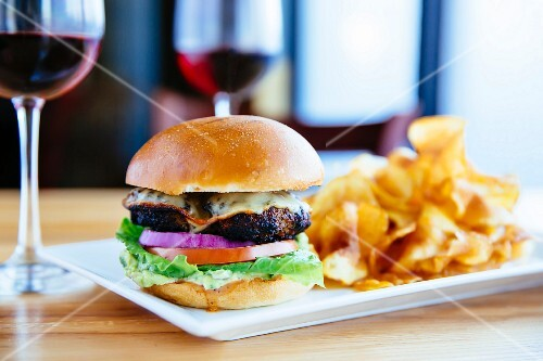 A cheeseburger with potato crisps and red wine on a table in a restaurant