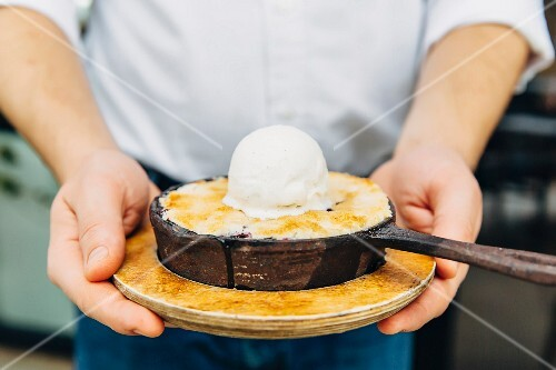 A waiter holding a small pan of dessert