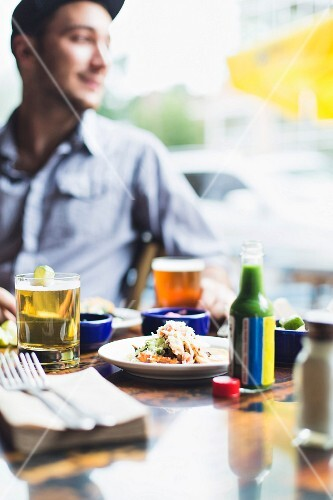 A young man sitting at a restaurant table with beer and food