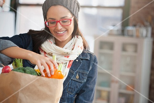 A young woman unpacking vegetables from a paper bag