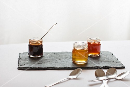 Various jars of honey on a slate platter