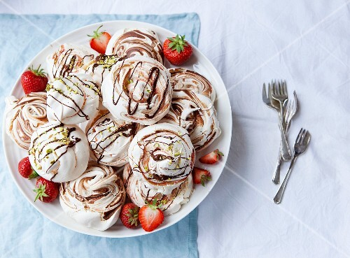 Various meringues with chocolate sauce, strawberries and pistachio nuts on a plate (seen from above)