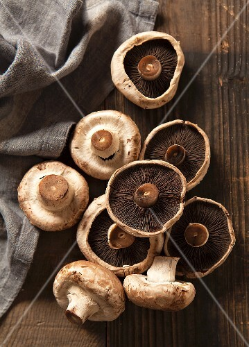 Nine mushrooms on a dark chopping board with a grey linen napkin
