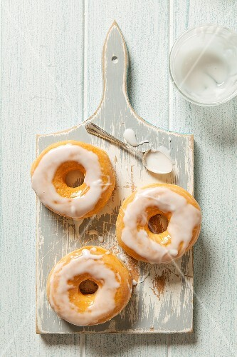 Three iced doughnuts on a grey wooden chopping board with a spoon