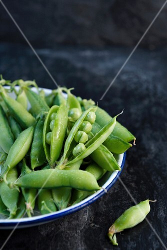 Freshly washed pea pods in an enamel bowl