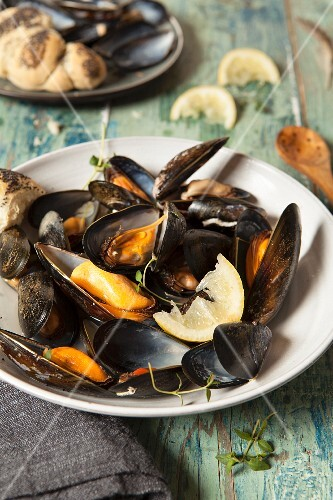 Mussels cooked in their shells served with poppy seed rolls, lemon and thyme
