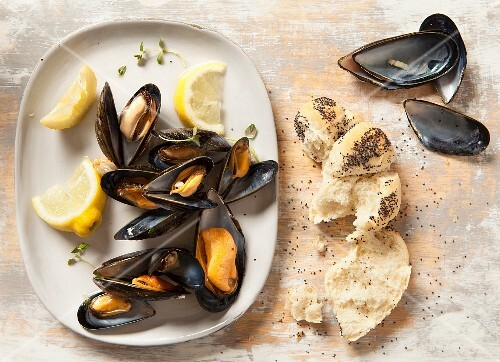 Mussels on an oval plate with lemon and fresh thyme