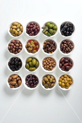 Various prepared olives in white bowls