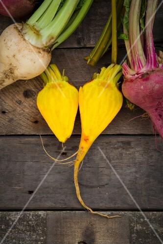 Organic beetroot, golden beets and white beets on a wooden surface (seen above)