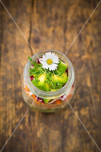 A layered salad in a jar with rice, vegetables and daisies (seen from above)
