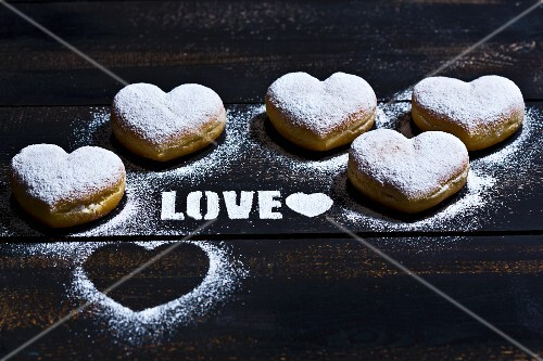 Heart-shaped doughnuts and the word Love in icing sugar on a wooden surface
