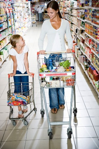 A mother and daughter with shopping trolleys walking down an aisle in a supermarket