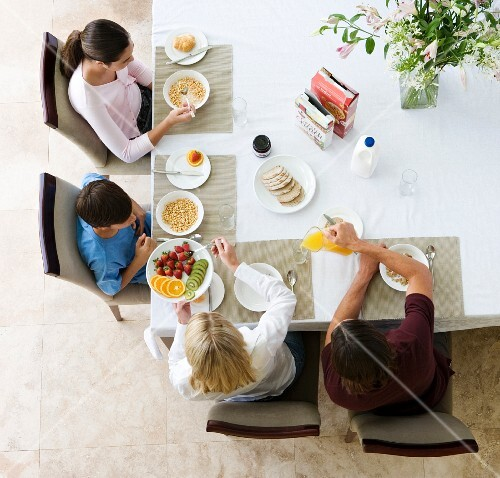 A family sitting at the breakfast table, seen from above
