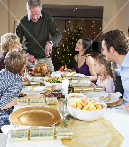A family eating a festive Christmas dinner with roast turkey, side dishes and crackers