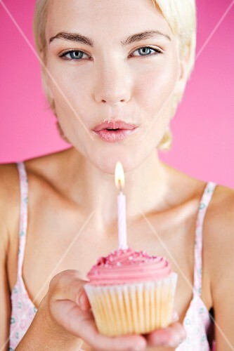 A young woman holding a birthday cupcake with a candle