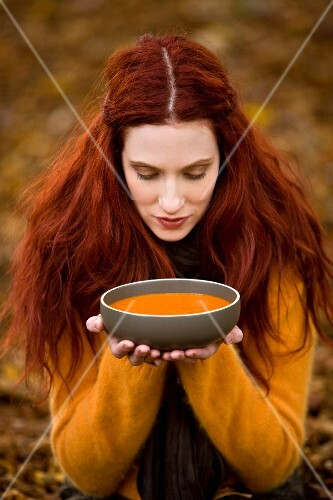 A redhaired woman wearing autumnal clothing holding a bowl of soup