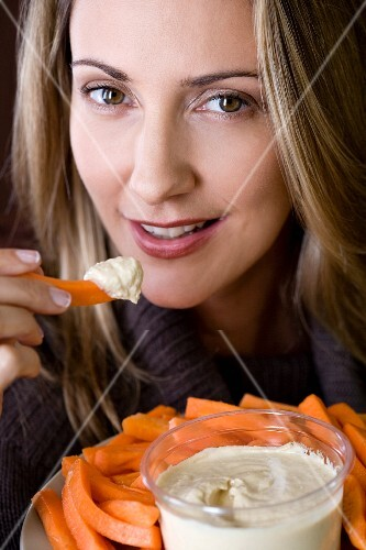 A woman eating carrot sticks with a dip