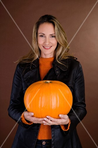 A woman holding an orange pumpkin