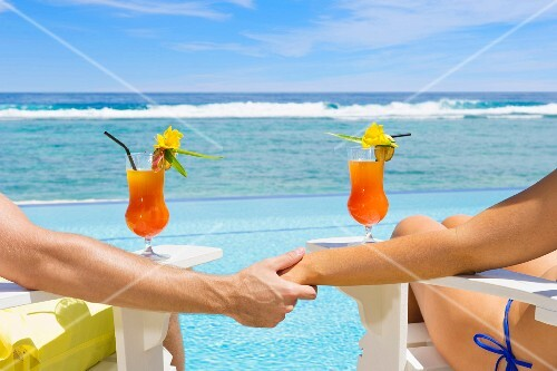 A couple holding hands and relaxing in loungers by the sea with cocktails