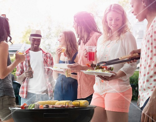 A group of multicultural young people having a barbecue outside
