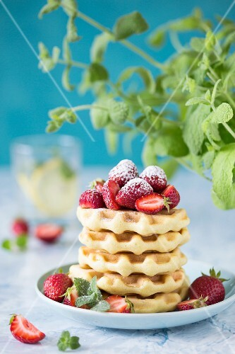 A sack of waffles with strawberries and icing sugar