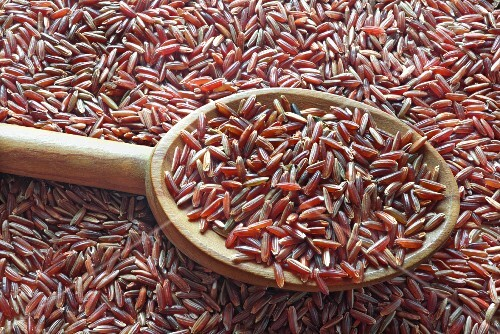 Red rice on a spoon on top of a pile of red rice