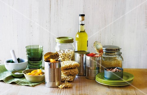 An arrangement of tinned fruit, pasta, dried beans, tinned tomatoes, oil, rice and tuna fish