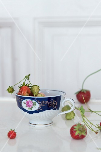 Strawberries in a porcelain cup white wooden surface