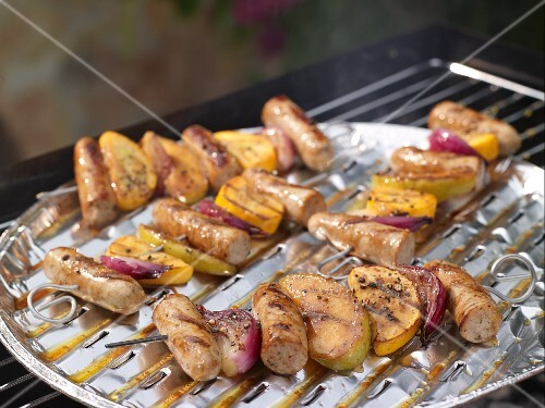 Colourful grilled sausage kebabs with onions and apples