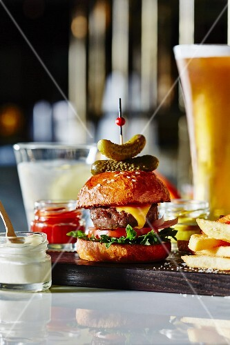 A beef slider with beer and chips