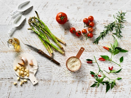 An arrangement of vegetables with asparagus, rosemary, oil and couscous