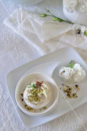 Mini pavlova with grated chocolate and chopped pistachio nuts next to decorative romantic flowers