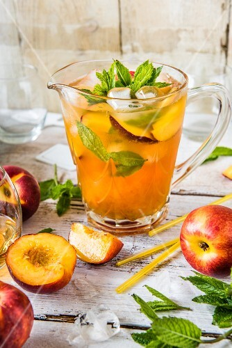 Iced tea with nectarines and mint in a glass jug