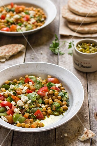 Chickpea salad made with broad beans, tomatoes, parsley and feta cheese next to green pepper relish