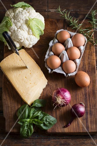 An arrangement of ingredients featuring cheese, eggs, cauliflower, herbs and onions