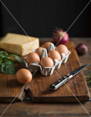 An arrangement of ingredients featuring eggs, cheese, herbs and onions