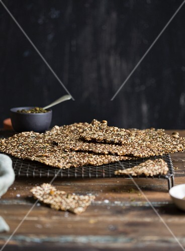 Homemade gluten-free seeded crackers on a wire rack